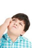 Muchacho que mira para arriba y rasguños su cabeza Foto de archivo libre de regalías
