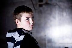 Muchacho que mira sobre el hombro contra backg del grunge Fotografía de archivo libre de regalías