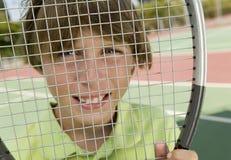 Muchacho que mira a través de la raqueta de tenis fotografía de archivo libre de regalías
