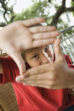 Muchacho que mira a través de las manos Foto de archivo