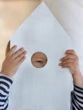 Muchacho que mira a través del agujero en casa de madera Imágenes de archivo libres de regalías