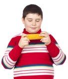 Muchacho que mira un maíz hervido Imágenes de archivo libres de regalías