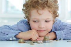 Muchacho que mira una pila de monedas El concepto de educación económica del ` s de los niños Imagen de archivo libre de regalías