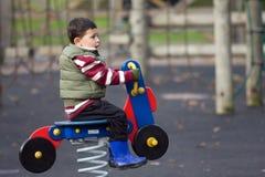 Muchacho que monta un juguete de madera Imagen de archivo libre de regalías