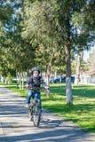 Muchacho que monta una bici en el parque Imagenes de archivo
