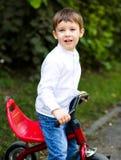 Muchacho que monta una bicicleta en el parque Foto de archivo libre de regalías