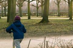 Muchacho que monta una vespa en un día de invierno frío en un parque Fotografía de archivo libre de regalías