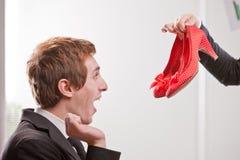 Muchacho que muestra felicidad al ver pares de zapatos rojos Fotos de archivo