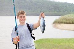 Muchacho que muestra un pescado foto de archivo libre de regalías