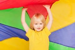 Muchacho que oculta debajo del toldo hecho del paracaídas del arco iris Imágenes de archivo libres de regalías
