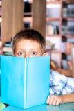 Muchacho que oculta detrás del libro Foto de archivo