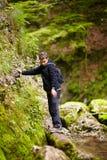 Muchacho que pasa sobre un río de la montaña Foto de archivo libre de regalías