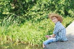 Muchacho que pesca con caña con la caña de pescar rústica de madera que se sienta en el puente concreto Fotos de archivo libres de regalías