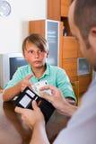 Muchacho que pide a padre dinero Fotos de archivo