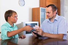 Muchacho que pide a padre dinero Imagen de archivo