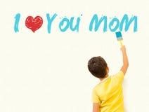 Muchacho que pinta te amo a la mamá con el cepillo en la pared Fotos de archivo libres de regalías