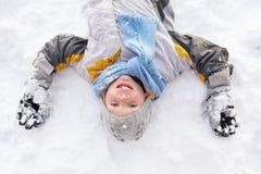 Muchacho que pone en el ángel de fabricación de tierra de la nieve Imágenes de archivo libres de regalías