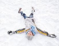 Muchacho que pone en el ángel de fabricación de tierra de la nieve Fotos de archivo