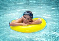 Muchacho que pone en el anillo de goma en piscina Imágenes de archivo libres de regalías