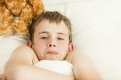 Muchacho que pone mala cara en la cama cubierta con la manta Fotografía de archivo