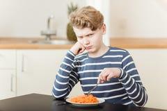 Muchacho que pone mala cara que se sienta delante de zanahorias destrozadas Imagen de archivo libre de regalías