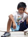 Muchacho que pone mala cara que se sienta en su patín Foto de archivo libre de regalías