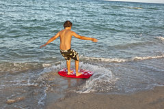 Muchacho que practica surf en la playa Imagenes de archivo