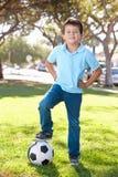 Muchacho que presenta con el balón de fútbol Imagen de archivo libre de regalías