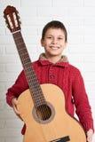 Muchacho que presenta con la guitarra acústica Imagen de archivo libre de regalías