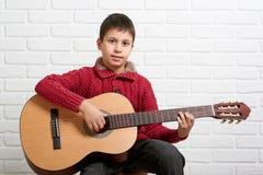 Muchacho que presenta con la guitarra acústica Foto de archivo