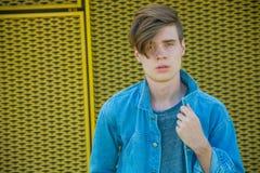 Muchacho que presenta en el dril de algodón azul, modelo adolescente Foto de archivo libre de regalías