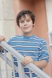 Muchacho que presenta en una escalera Imagenes de archivo