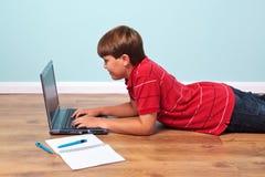 Muchacho que pulsa en su computadora portátil Fotos de archivo