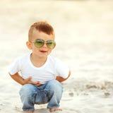 Muchacho que ríe en la arena fotografía de archivo