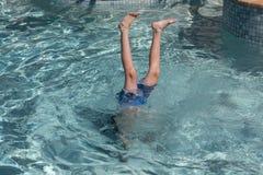 Muchacho que realiza posición del pino en piscina Imagen de archivo libre de regalías