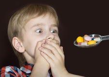 Muchacho que rechaza tomar la medicina Imagen de archivo