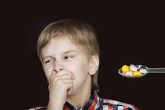 Muchacho que rechaza tomar la medicina Imagenes de archivo