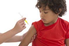 Muchacho que recibe la vacuna en el brazo imagenes de archivo