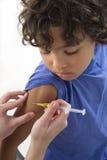 Muchacho que recibe la vacuna en el brazo fotos de archivo libres de regalías