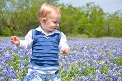 Muchacho que recorre en flores Foto de archivo