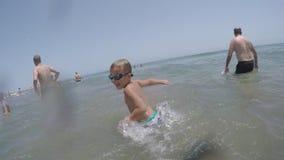 Muchacho que salpica el agua al bañarse en el océano durante vacaciones en Gran Canaria almacen de video