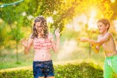 Muchacho que salpica a la muchacha con el arma de agua, jardín soleado del verano Imagen de archivo libre de regalías