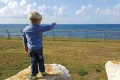 Muchacho que señala en las naves en el mar Fotografía de archivo libre de regalías