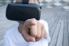 Muchacho que señala en una cámara y que mira a través de las gafas de VR Imágenes de archivo libres de regalías
