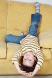 Muchacho que se acuesta en el sofá en el país Imagenes de archivo