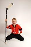 Muchacho que se arrodilla con el palillo de hockey Fotos de archivo