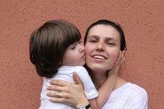 Muchacho que se besa abrazando a la madre Fotografía de archivo libre de regalías