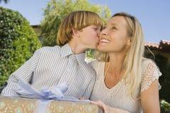 Muchacho que se besa en la mejilla de la madre Fotografía de archivo libre de regalías