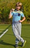 Muchacho que se coloca con la estafa y la bola de tenis en la corte Imagen de archivo libre de regalías