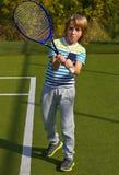 Muchacho que se coloca con la estafa y la bola de tenis en la corte Fotografía de archivo libre de regalías